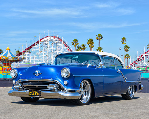 AUT 21 RK3648 01 © Kimball Stock 1954 Oldsmobile 2-Door Hard Top Blue And White 3/4 Front View By Amusement Park