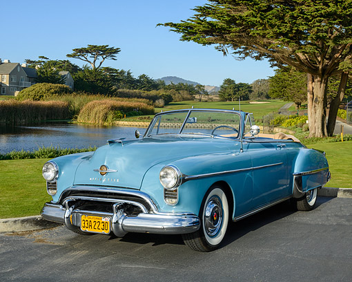 AUT 21 RK3672 01 © Kimball Stock 1950 Oldsmobile 88 Convertible Blue 3/4 Front View By Lake And Trees