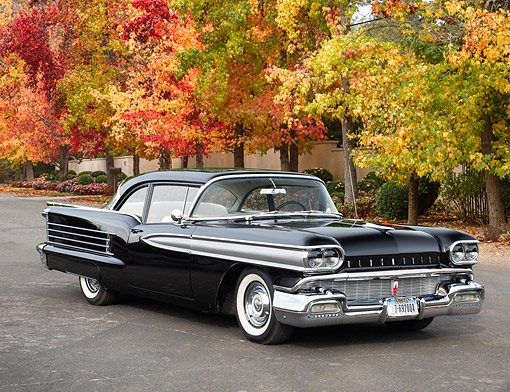 AUT 21 RK3738 01 © Kimball Stock 1958 Oldsmobile Dynamic 88 Black 3/4 Front View By Autumn Trees