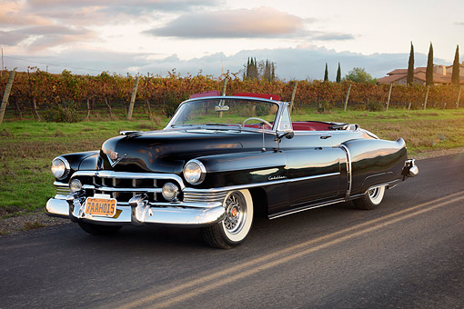 AUT 21 RK3752 01 © Kimball Stock 1950 Cadillac Series 62 Convertible Black 3/4 Front View On Road By Vineyards