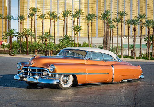 AUT 21 RK3762 01 © Kimball Stock 1951 Cadillac Coupe DeVille Series 62 Custom Copper And Pearl 3/4 Front View By Palm Trees And Building