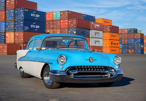 AUT 21 RK3767 01 © Kimball Stock 1955 Oldsmobile Rocket 88 Blue 3/4 Front View By Shipping Crates