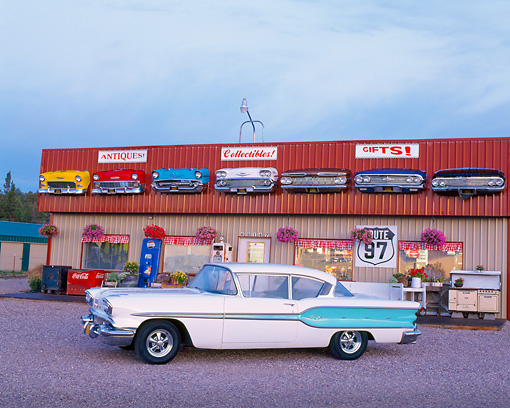AUT 21 RK0095 04 © Kimball Stock 1958 White & Lt Blue Pontiac Chieftain 3/4 Side Front Of Trading Post Store Lights On