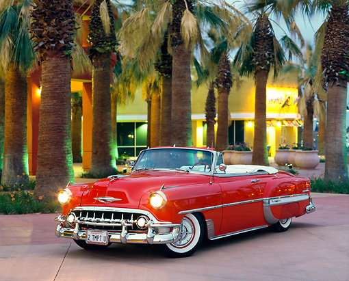 AUT 21 RK0126 02 © Kimball Stock 1953 Red Chevy Bel Air Convertible Custom 3/4 Front On Pavement By Palm Trees & Building At Dusk Headlights On