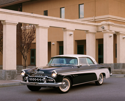 AUT 21 RK0130 08 © Kimball Stock 1955 Black And White De Soto Fireflite 3/4 Front On Pavement By Building Headlights On