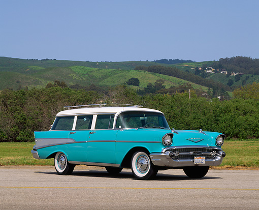 AUT 21 RK0165 03 © Kimball Stock 1957 Chevy Bel Air Station Wagon Turquoise 3/4 Side View On Pavement By Grass And Hills Blue Sky