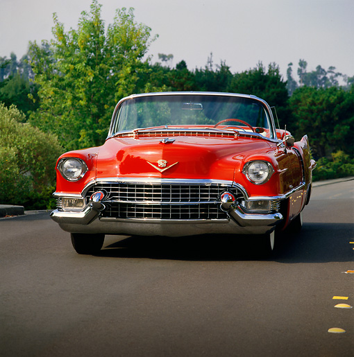 AUT 21 RK0202 02 © Kimball Stock 1955 Cadillac Convertible Red Head On View On Pavement By Trees