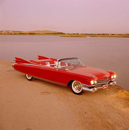 AUT 21 RK0223 05 © Kimball Stock 1959 Cadillac Eldorado Convertible Red Overhead 3/4 Side View On Dirt Headlights On By Lake At Dusk