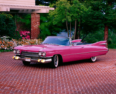 AUT 21 RK0255 04 © Kimball Stock 1959 Pink Cadillac Convertible 3/4 Front On Brick Pavement Headlights On By Trees & Flowers Filtered