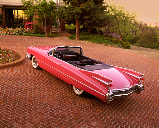 AUT 21 RK0259 04 © Kimball Stock 1959 Cadillac Convertible Pink Overhead 3/4 Rear On Brick Driveway At Dusk