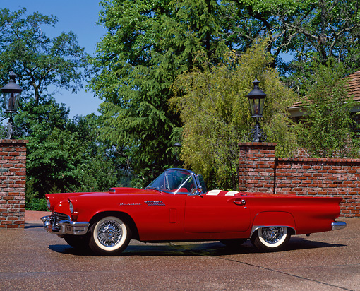 AUT 21 RK0271 03 © Kimball Stock 1957 Ford Thunderbird E Type Red Convertible 3/4 Front View On Pavement By Brick Wall Trees