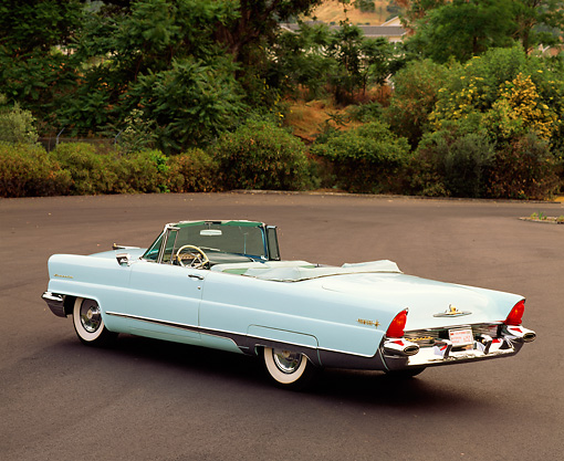 AUT 21 RK0274 02 © Kimball Stock 1956 Lincoln Premier Convertible Light Blue 3/4 Rear View On Pavement By Trees And Bushes