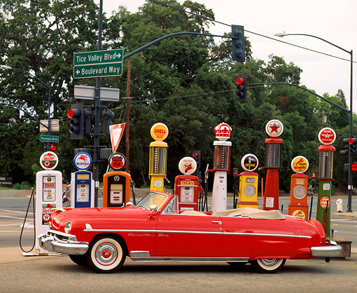 AUT 21 RK0277 05 © Kimball Stock 1951 Red Lincoln Convertible Cosmopolitan Side View By Different Old Gas Pumps On Street Corner