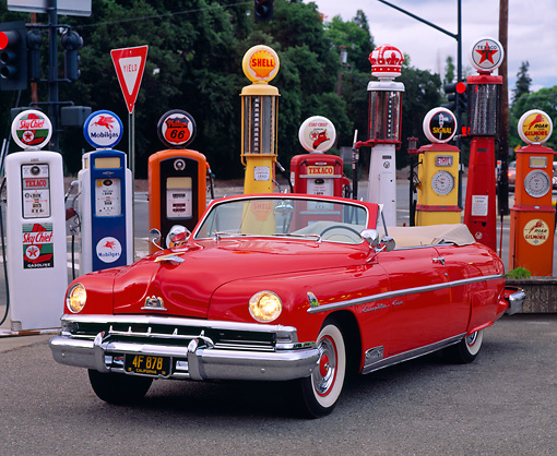AUT 21 RK0280 02 © Kimball Stock 1951 Red Lincoln Convertible Cosmopolitan 3/4 Front View By Different Old Gas Pumps Headlights On At Dusk