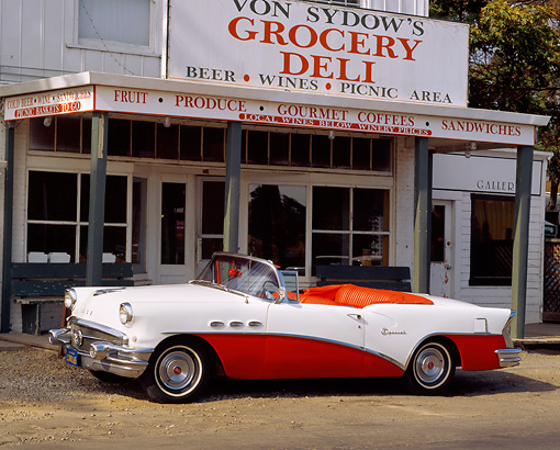 AUT 21 RK0293 09 © Kimball Stock 1956 Buick Special Convertible Red And White 3/4 Front View On Pavement By Store