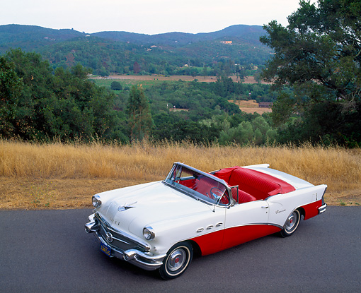 AUT 21 RK0294 06 © Kimball Stock 1956 Red And White Buick Special Convertible 3/4 Overhead 3/4 Front On Pavement By Dry Grass