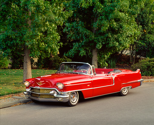 AUT 21 RK0336 03 © Kimball Stock 1956 Red Cadillac Convertible 3/4 Side On Road By Grass And Trees Headlights On