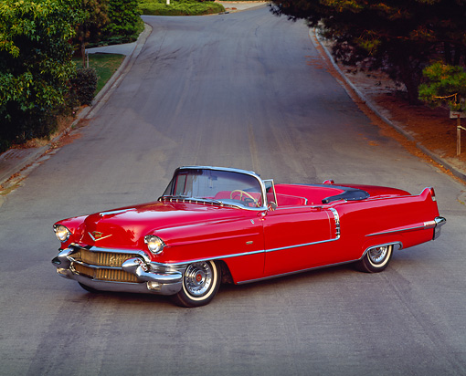 AUT 21 RK0336 05 © Kimball Stock 1956 Red Cadillac Convertible 3/4 Side On Road By Grass And Trees Headlights On