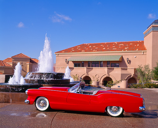 AUT 21 RK0348 05 © Kimball Stock 1953 Red Plymouth Belmont Convertible Side View In Front Of Water Fountain Blue Sky