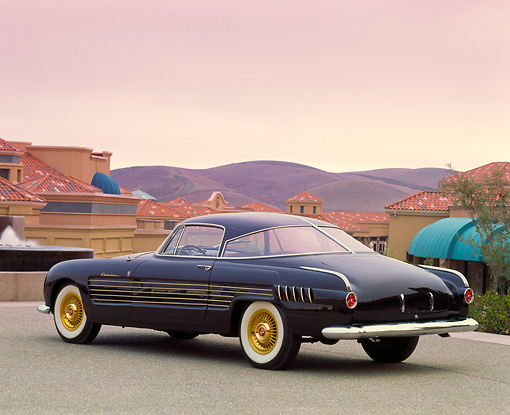 AUT 21 RK0352 07 © Kimball Stock 1953 Black Cadillac Ghia Coupe 3/4 Rear View By Water Fountain And Buildings At Dusk