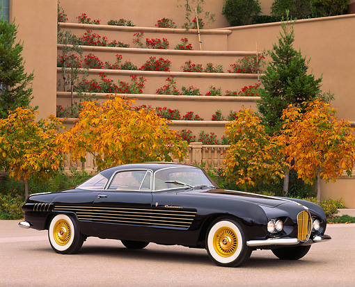 AUT 21 RK0357 03 © Kimball Stock 1953 Black Cadillac Ghia Coupe 3/4 Side View On Pavement By Building And Fall Trees