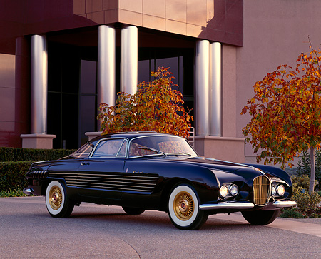 AUT 21 RK0358 01 © Kimball Stock 1953 Cadillac Ghia Coupe Black 3/4 Side View By Building And Fall Trees