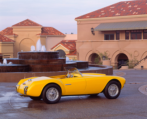 AUT 21 RK0376 09 © Kimball Stock 1953 Yellow Siata Spyder Convertible 3/4 Rear On Wet Pavement By Fountain And Buildings