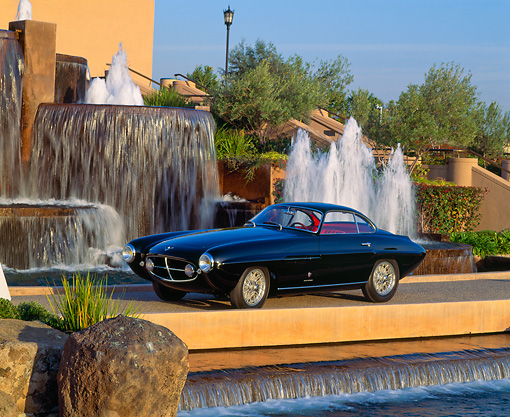 AUT 21 RK0385 02 © Kimball Stock 1953 Black Fiat Ghia Coupe BV 3/4 Side View In Front Of Water Fountain Blue Sky