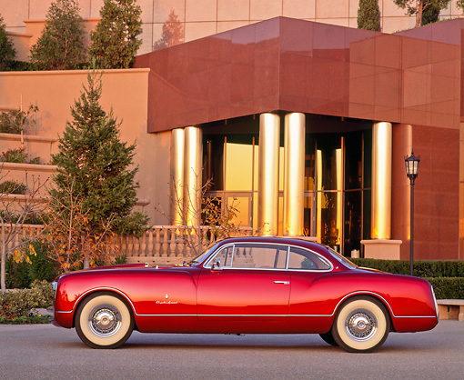 AUT 21 RK0389 01 © Kimball Stock 1953 Burgundy Chrysler Sport Coupe Side View In Front Of Museum At Dusk