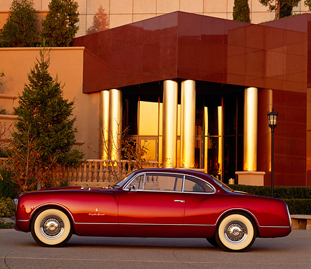 AUT 21 RK0390 17 © Kimball Stock 1953 Chrysler Sport Coupe Burgundy Profile In Front Of Lighted Museum At Dusk