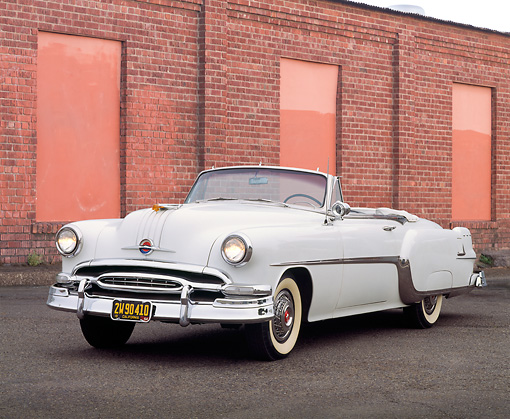 AUT 21 RK0400 08 © Kimball Stock 1954 White Pontiac Star Chief Convertible 3/4 Front View On Pavement By Wall Headlights On