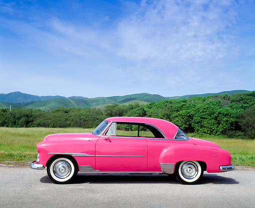 AUT 21 RK0411 04 © Kimball Stock 1951 Custom Pink Chevrolet Side View On Pavement By Grass And Hills Blue Sky