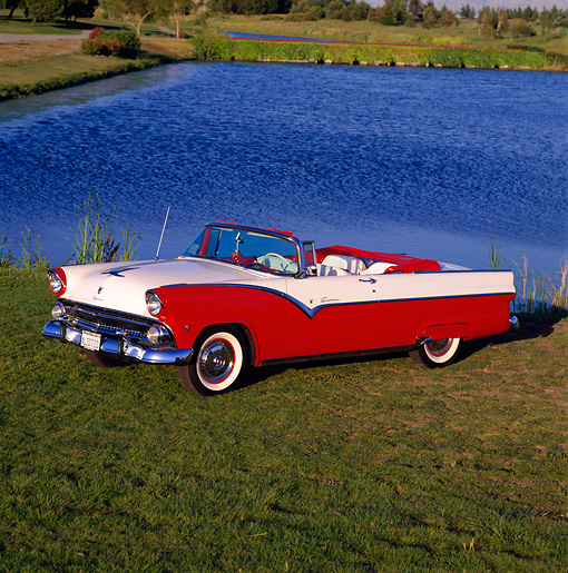 AUT 21 RK0422 05 © Kimball Stock 1955 Ford Sunliner Convertible Red And White Side 3/4 View On Grass By Lake