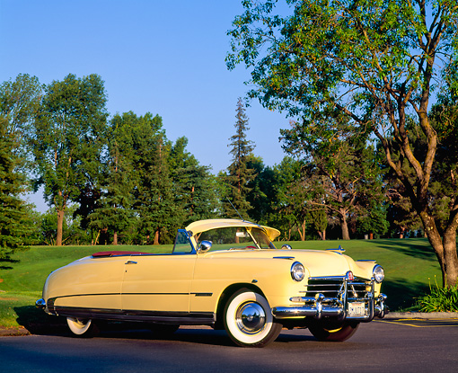 AUT 21 RK0445 04 © Kimball Stock 1950 Yellow Hudson Commodore Convertible 3/4 Side View By Grass And Trees Blue Sky