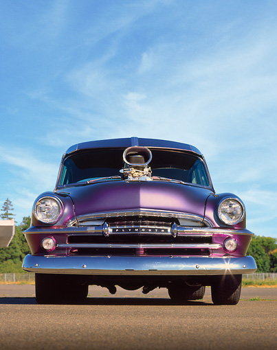 AUT 21 RK0458 02 © Kimball Stock 1954 Plymouth Savoy Custom Purple Low Head On Shot On Pavement Blue Sky