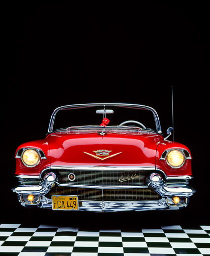 AUT 21 RK0475 02 © Kimball Stock 1956 Red Cadillac Convertible Head On View On Checkerboard Headlights On Studio