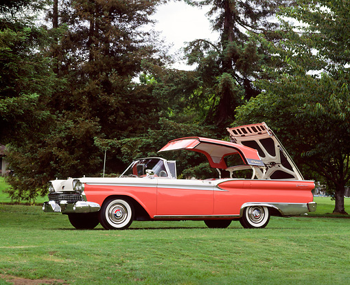 AUT 21 RK0530 01 © Kimball Stock 1959 Ford Galaxie Skyliner Roof Retracting 3/4 Front View On Grass By Trees