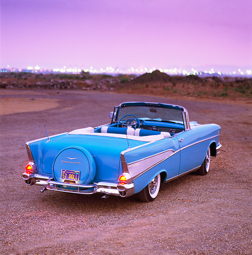 AUT 21 RK0603 04 © Kimball Stock 1957 Chevrolet Bel Air Convertible Light Blue Overhead 3/4 Rear View On Dirt City Lights At Night