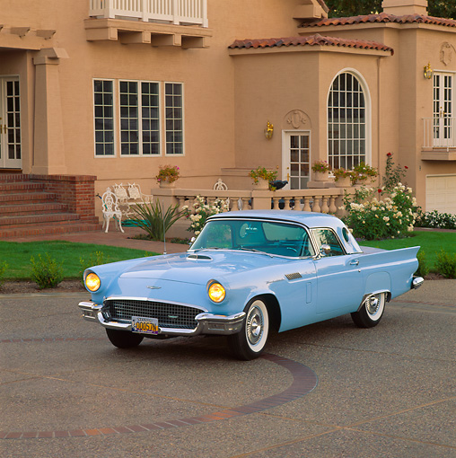 AUT 21 RK0626 07 © Kimball Stock 1957 Ford Thunderbird Powder Blue 3/4 Side View On Pavement In Front Of House Headlights On