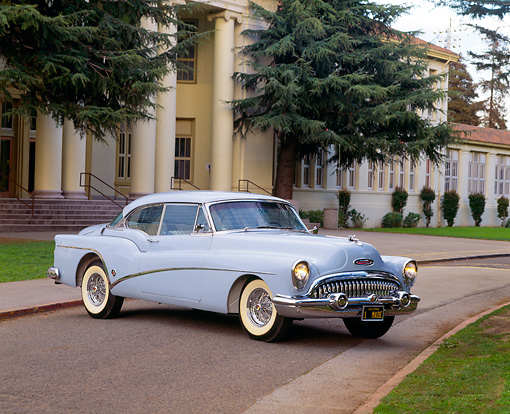 AUT 21 RK0642 05 © Kimball Stock 1953 Buick Skylark Hardtop Light Blue 3/4 Front View On Pavement By Trees And Building