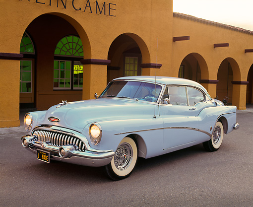 AUT 21 RK0643 02 © Kimball Stock 1953 Buick Skylark Hardtop Light Blue 3/4 Side View On Pavement In Front Of Building Headlights On