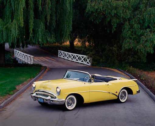 AUT 21 RK0668 05 © Kimball Stock 1954 Buick Skylark Model 100 Convertible Yellow 3/4 Side View On Pavement
