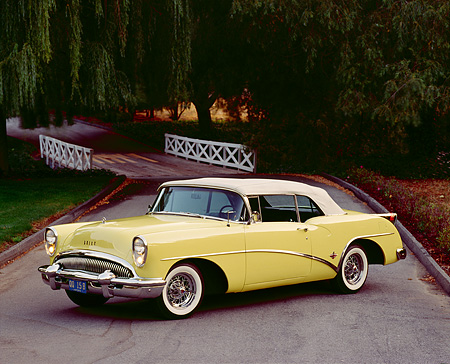 AUT 21 RK0669 02 © Kimball Stock 1954 Buick Skylark Model 100 Convertible Yellow 3/4 Side View On Pavement By Bridge