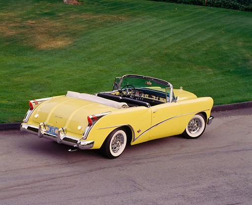 AUT 21 RK0671 03 © Kimball Stock 1954 Buick Skylark Model 100 Convertible Yellow 3/4 Rear Overhead On Pavement By Grass