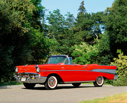 AUT 21 RK0676 09 © Kimball Stock 1957 Chevy Bel Air Fuel Injection Convertible Red 3/4 Side View On Pavement By Trees Blue Sky