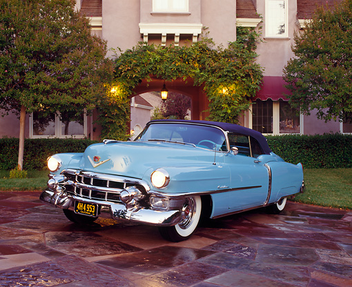 AUT 21 RK0684 03 © Kimball Stock 1953 El Dorado Cadillac Light Blue 3/4 Front View On Driveway Headlights On By House And Trees At Dusk