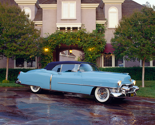 AUT 21 RK0686 09 © Kimball Stock 1953 Cadillac El Dorado Light Blue 3/4 Side View By House And Trees