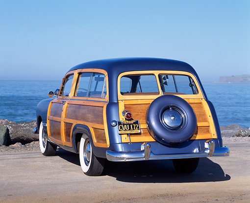 AUT 21 RK0696 03 © Kimball Stock 1950 Ford Woody Station Wagon Blue 3/4 Rear View On Pavement By Ocean Blue Sky
