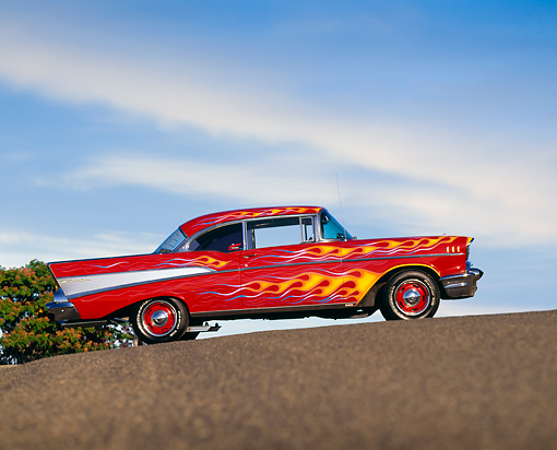 AUT 21 RK0710 04 © Kimball Stock 1957 Chevrolet Bel Air Red With Flames Slanted Side View On Pavement Blue Sky