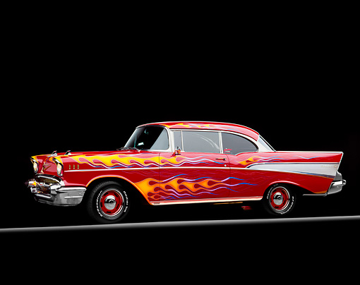 AUT 21 RK0715 01 © Kimball Stock 1957 Chevy Bel Air Red With Flames 3/4 Side View On Red And Yellow Lines Headlights On Studio